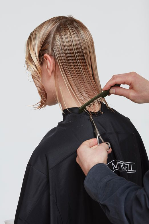 8. Begin the cut in the back. Take 1-inch diagonal sections to mimic the cutting line. Work up the head to the guide, point cutting to soften ends.