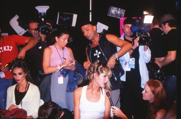 Backstage photo taken at the Betsey Johnson 2004 NY Fashion Week show, with Italo Gregorio In action for Warren-Tricomi.  He had to give an interview as he worked, cameras were flashing away.