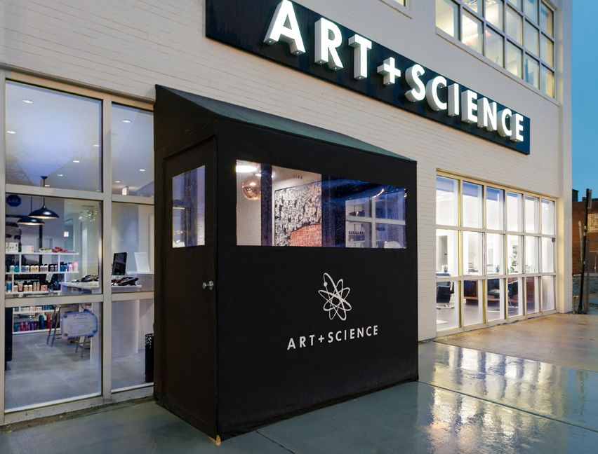 A valet greets guests to Art + Science West Loop while fresh white paint and backlit signage draws the eye to the business' exterior.