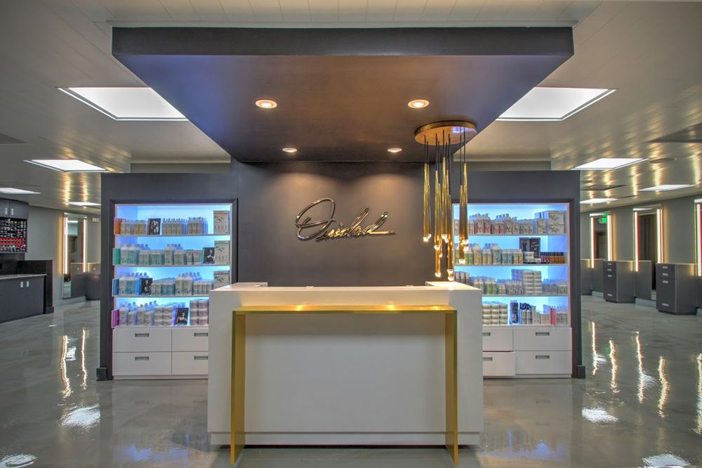 A huge modern light fixture gracefully illuminates the front desk. The gold of the fixture was inspired by the gold packaging of the salon's products.