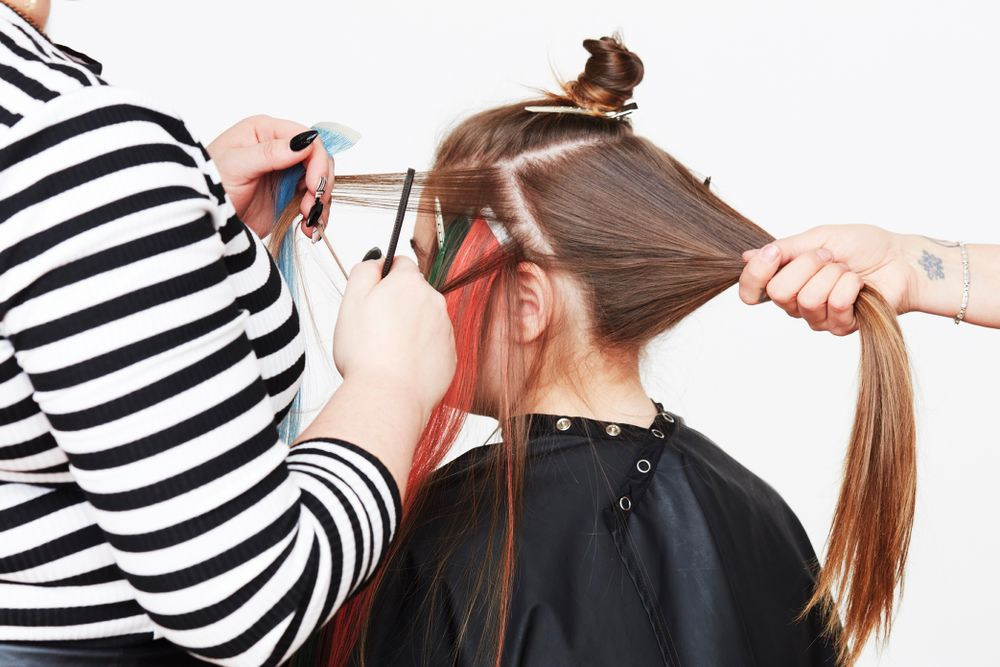 STEP 4. Extensions are placed on the diagonal to prevent drag and to allow for an updo. Use a tail comb to take a fine section and elevate from the head.