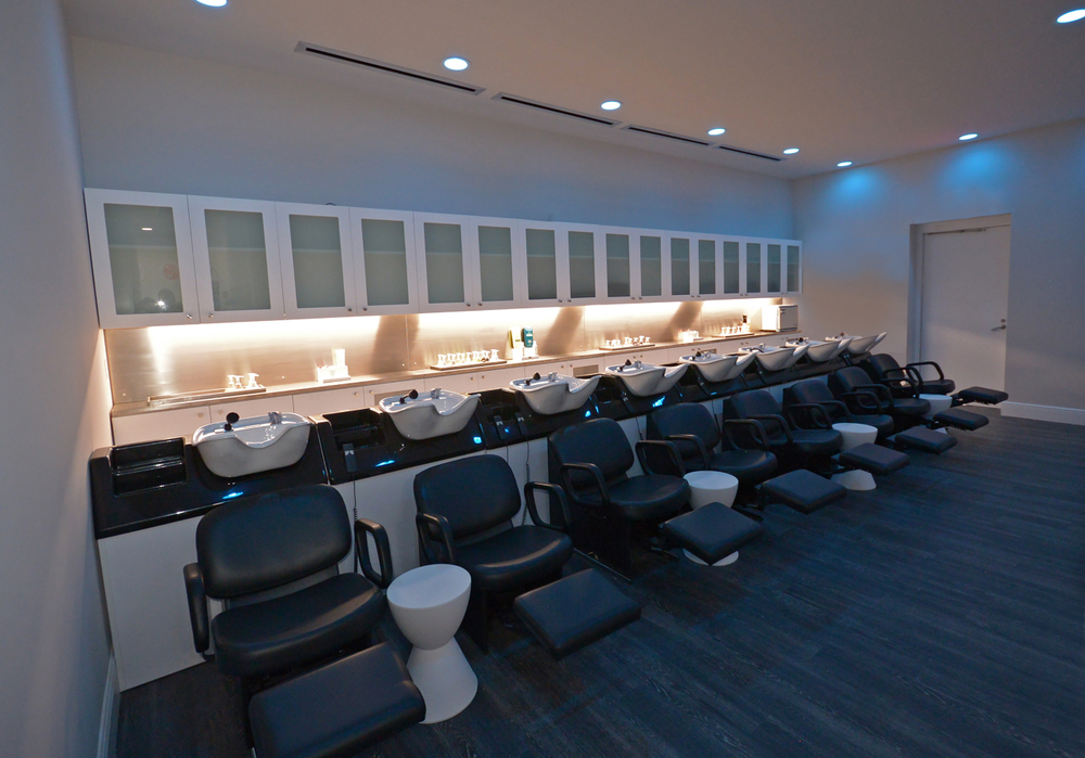 <p>A blue-lit dark shampoo room was designed to give clients a relaxing experience. Soft music plays in the background and each client receives a massage and steamed towel for their hair, along with a lip touch up.</p>