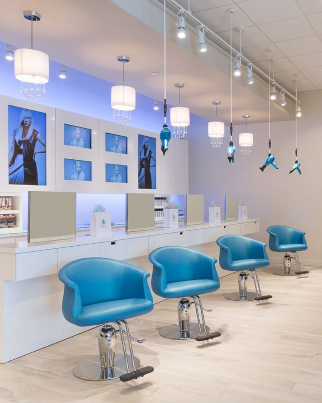 Suspended teal dryers match the chairs at the blowdry bar.