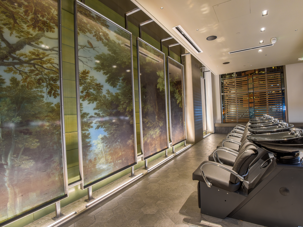 A woodland scene on backlit screens adds to the serenity of the glassed-in shampoo oasis.