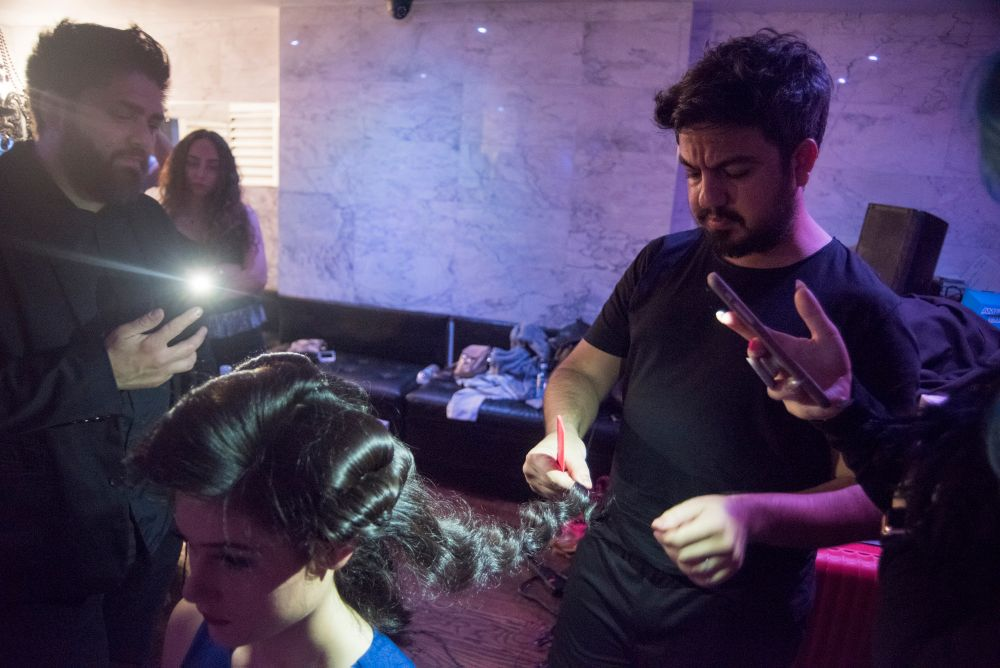 Avci creates his signature glam waves on a model backstage.