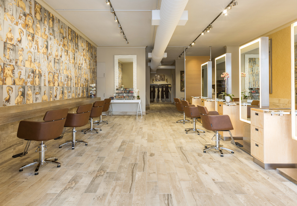 An accent wall across from the styling stations features anique, gold-foiled wallpaper from Trove.