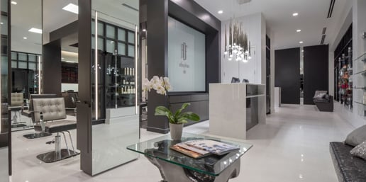 An onyx reception desk under stalactite pendant lighting greets guests to Anthony DeFranco Salon and Spa.