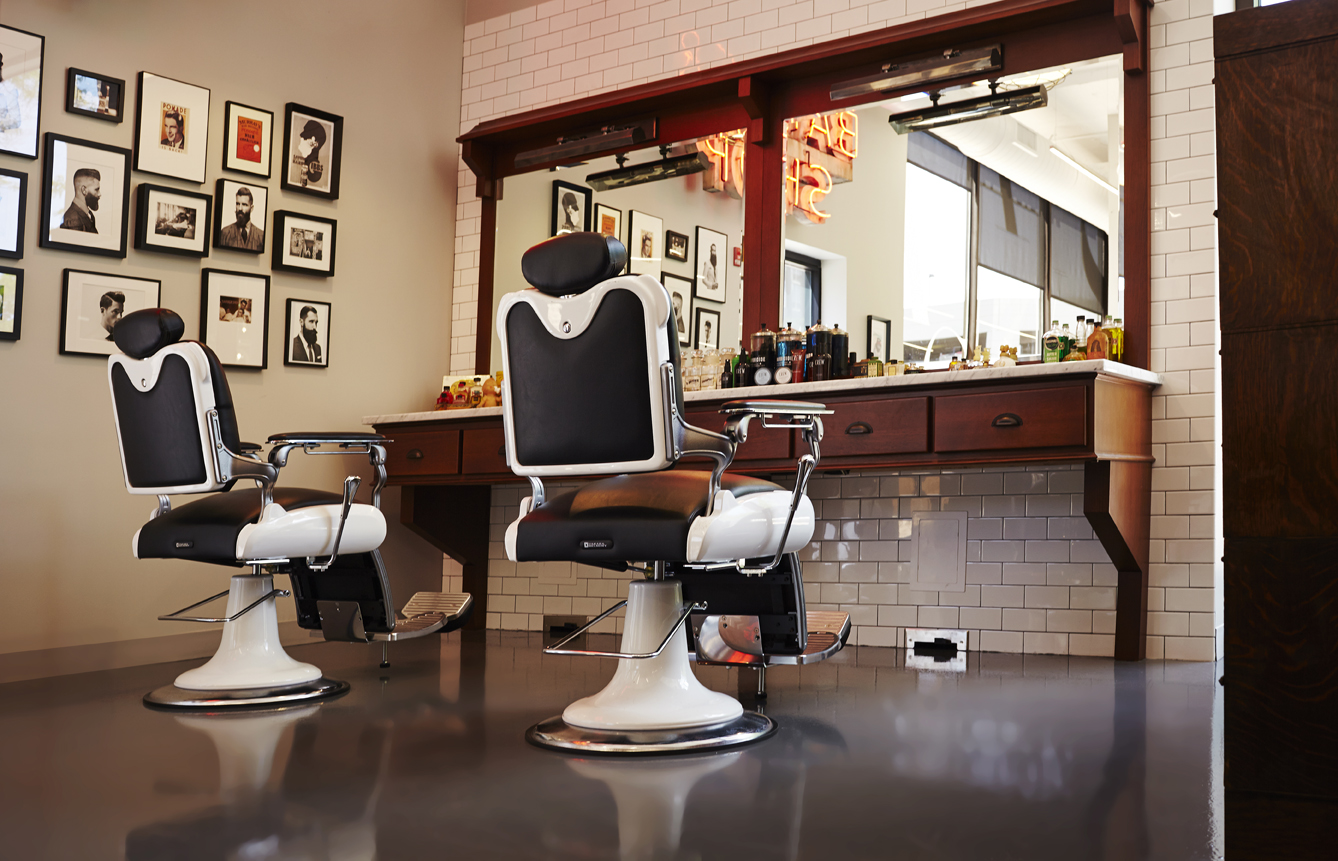 Two barbering chairs, oak stations, and American Crew imagery set a distinct masculine tone in the space.