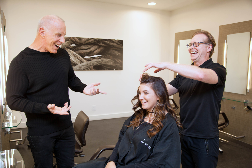 Adam Broderick and Stylist Bill Schrlau, share a laugh with a client at Adam Broderick Salon and Spa.