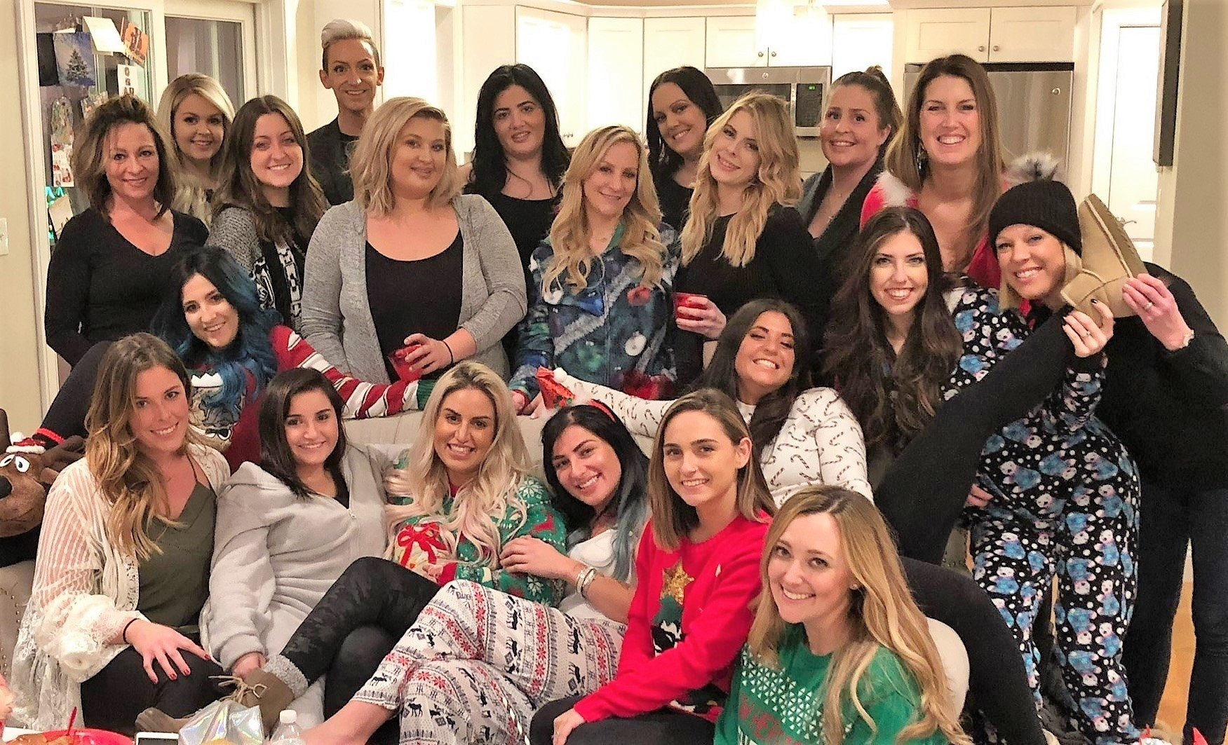 The lives of Amanda Barror (center, bottom) and her happy tribe at the two Aqua Salon and Spas have changed for the better thanks to online booking. Now there's more time for bonding experiences like a holiday pajama party!