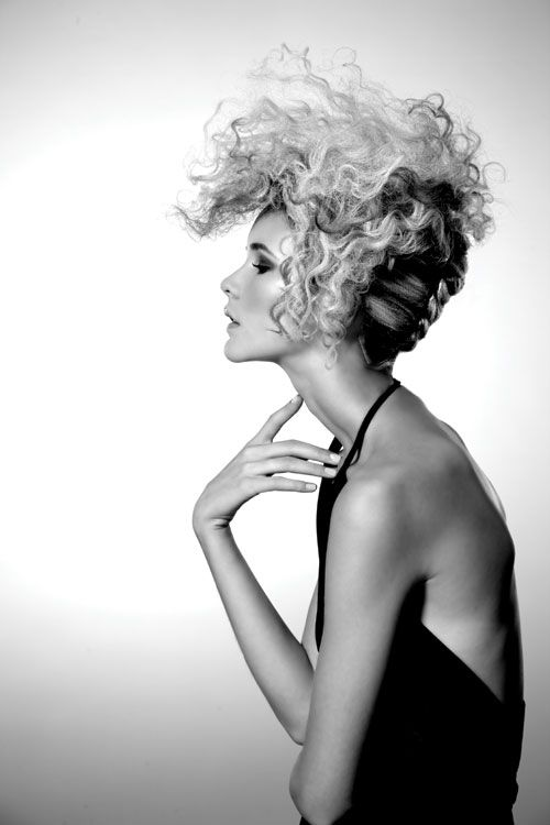 Movement and Texture ::  Conscious of the fact that not every client desires a dramatic short cut, the team exposed two gender-mixing techniques to long hair by adding texture. For fine blonde hair, a twist in back and forward-moving curl texture in front suggests androgyny merged with the '50s.