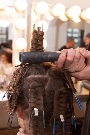 STEP 3: Hold each section with a flatiron for 15 to 20 seconds to set the shape. Once cool, gently release the pins and brush hair with a wide-toothed comb.