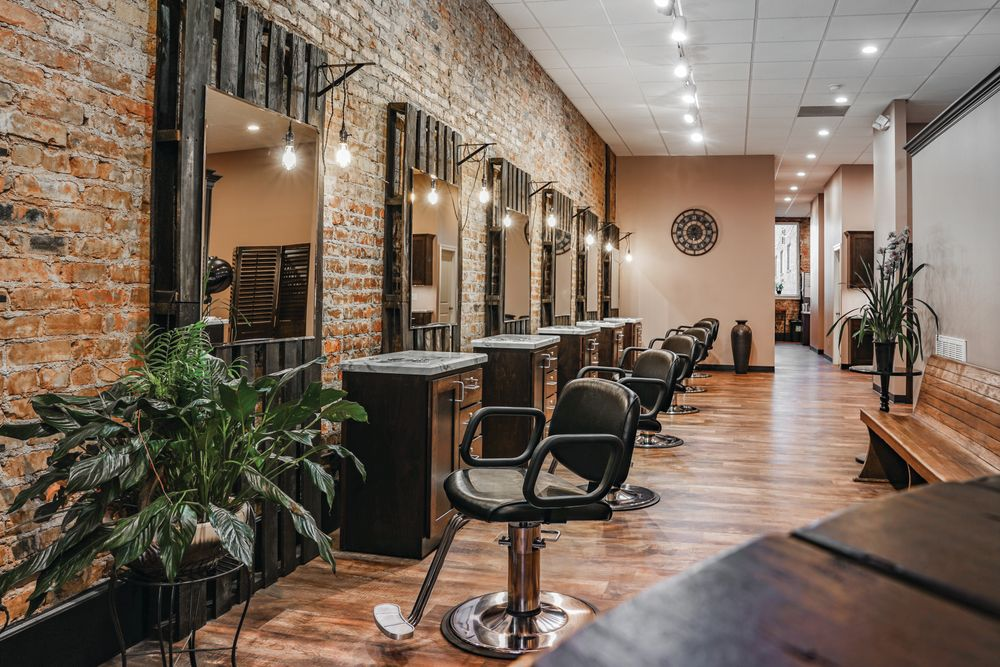 "<a href=""https://www.aspirewv.com/"" target=""_blank"" rel=""noopener"">Aspire Salon</a> in Parkersburg, West Virginia, chose repurposed wood throughout, including an antique church pew, to create an earthy and inviting vibe. The original brick from the early 1900s was purposefully left exposed and transports clients to a more relaxing era."