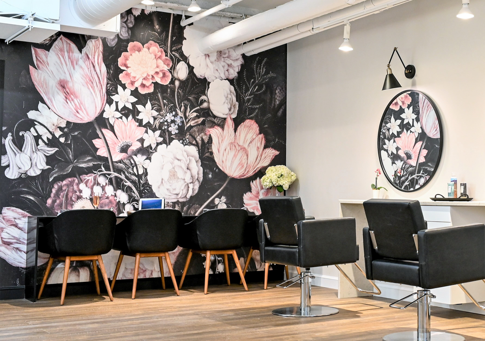 A bemusing floral wall mural behind the processing table ushers in blush pinks and corals into Atelier in Wellesley, Massachusetts.