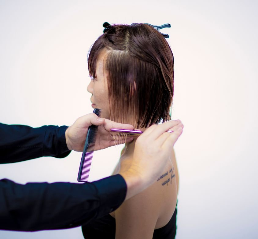 CUTTING TECHNIQUE: STEP 3 - Release the perimeter line, comb and release the pressure from the ear with the comb and cut inside your fingers. Connecting the side section to the back sections. (Release the triangles on the side, divide in horizontal sections. Comb the hair with natural fall distribution and release the pressure from the ear with the comb). (Cut the hair in a horizontal line connected to the length in the nape area).