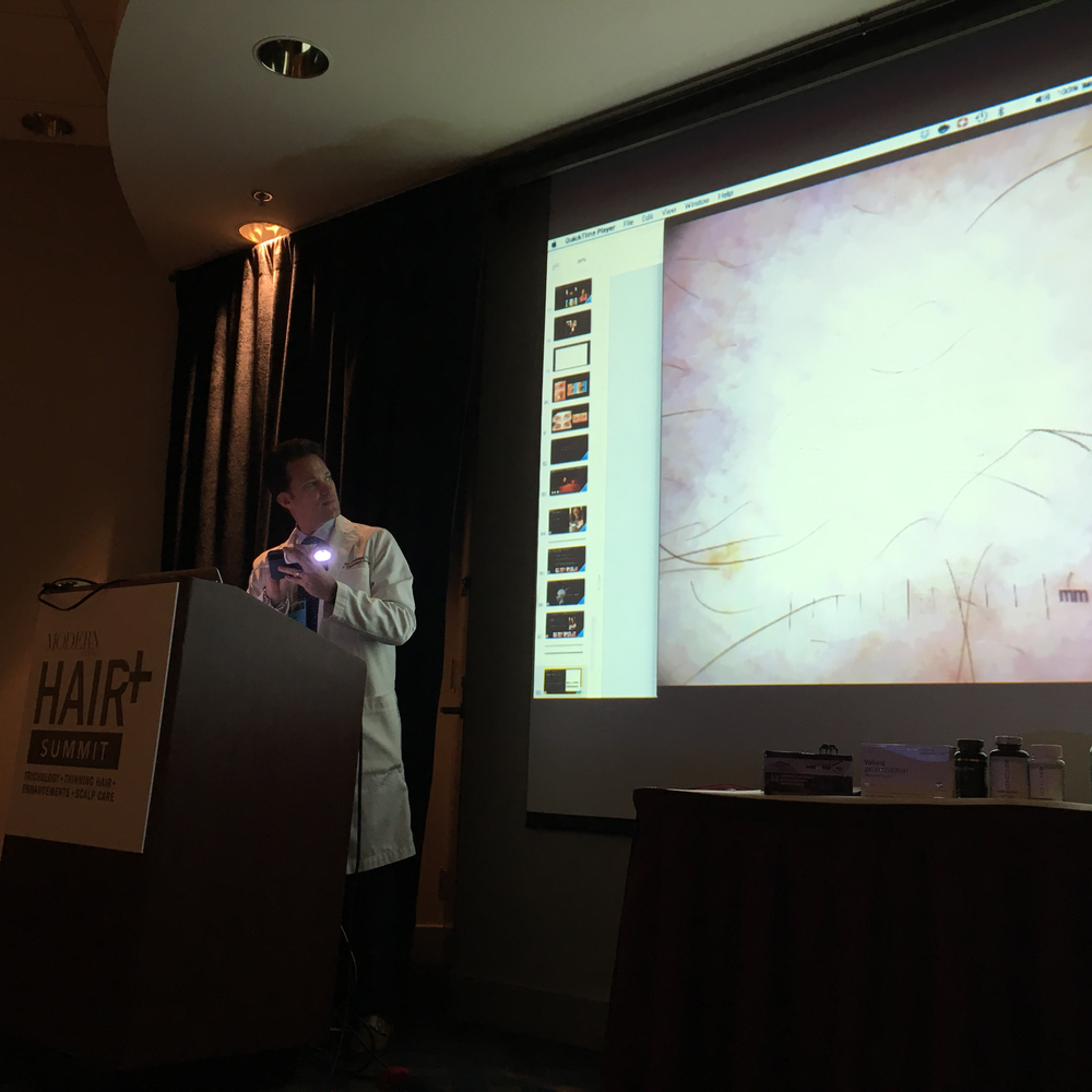 Demonstrating on the back of his hand, Dr. Alan Bauman shows how using a dual-polarized HairCam lens and Apple TV turns his iPhone into a scalp microscope, giving clients a close-up look at their scalp situation.