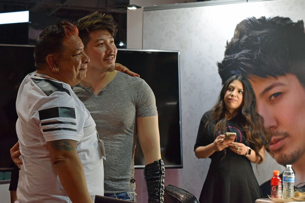 Guy Tang poses with a fan at his meet-and-greet at the Bellami booth.