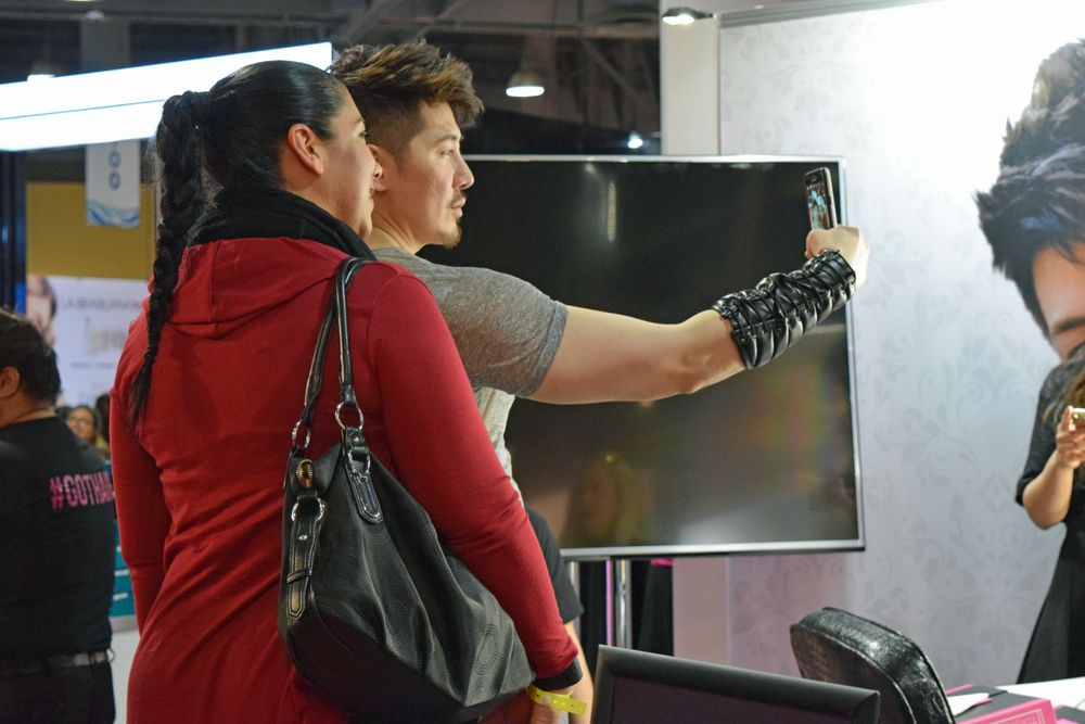 Guy Tang helps an attendee find the perfect selfie lighting at the Bellami/Guy Tang meet and greet on the show floor.