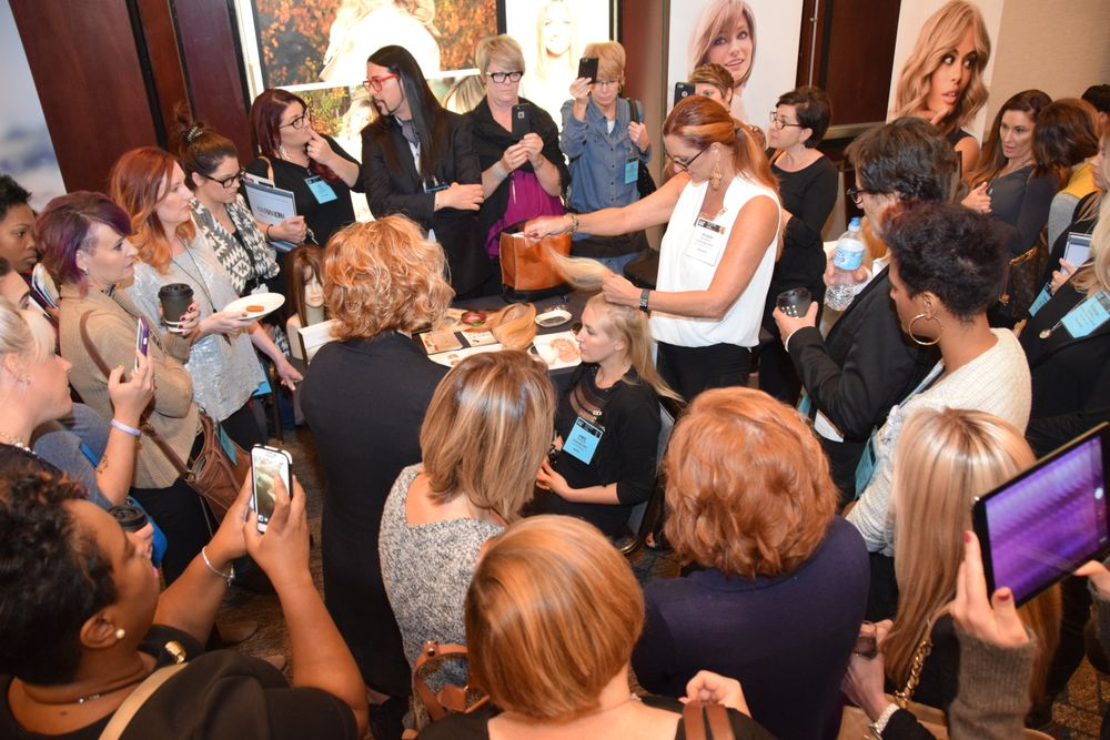 With cameras in hand, attendees swarm Easihair Pro's exhibition table while Bobbi Russell demonstrates a hair system applicaiton.