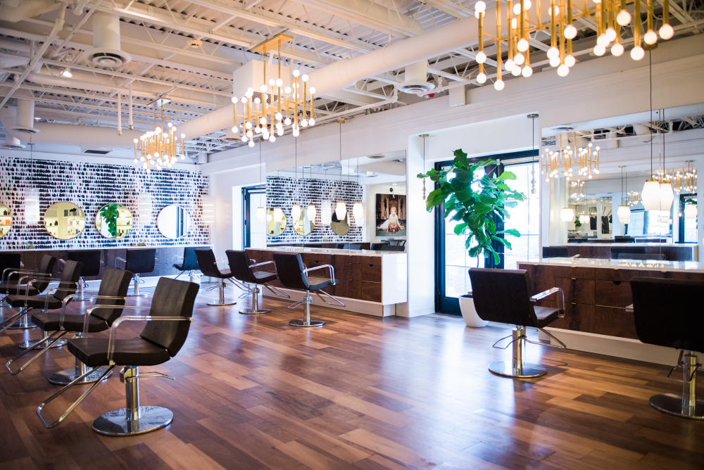 The Coopers chose to preserve some of the salon's history by refinishing the existing floors and brightened up the space with Jonathan Adler chandeliers and pendant task lighting. Mick Jagger's Queen of Spain wallpaper on the back wall invites clients to explore the new design.