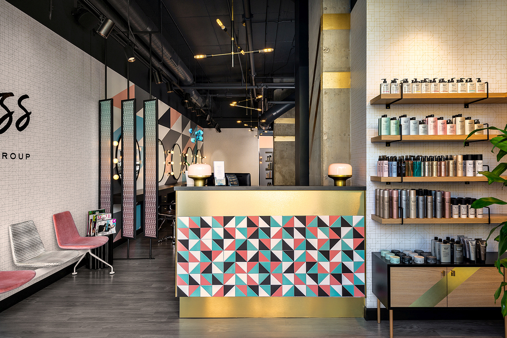 Salmon, teal, black and white tiles adorn the brass-accented front desk at Boss Hair Group in Chicago, while fun pink seating invites guests to stay a while.