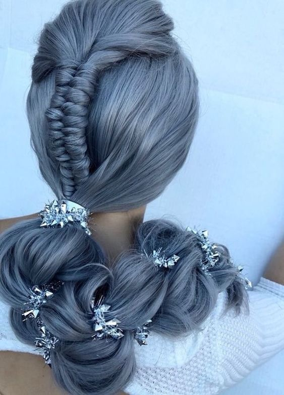 <p>To create this look Garcia took a triangle section at the top of the head to create an infiniti braid, incorporating the braid and the remaining of the hair into a low pony. She then added a silver shiny hair jewelry into a three strand braid and expanded the braid giving it texture and separation.</p>