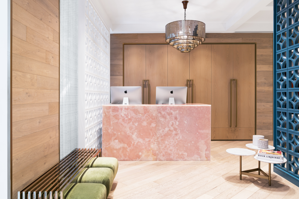A pink onyx front desk pairs with green poufs and a blue separation wall at Butter Beauty Parlour in Calgary, Alberta.