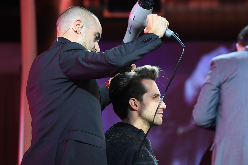 Samy Petot uses a blow dryer on stage at the brand's 25 anniversary celebration.