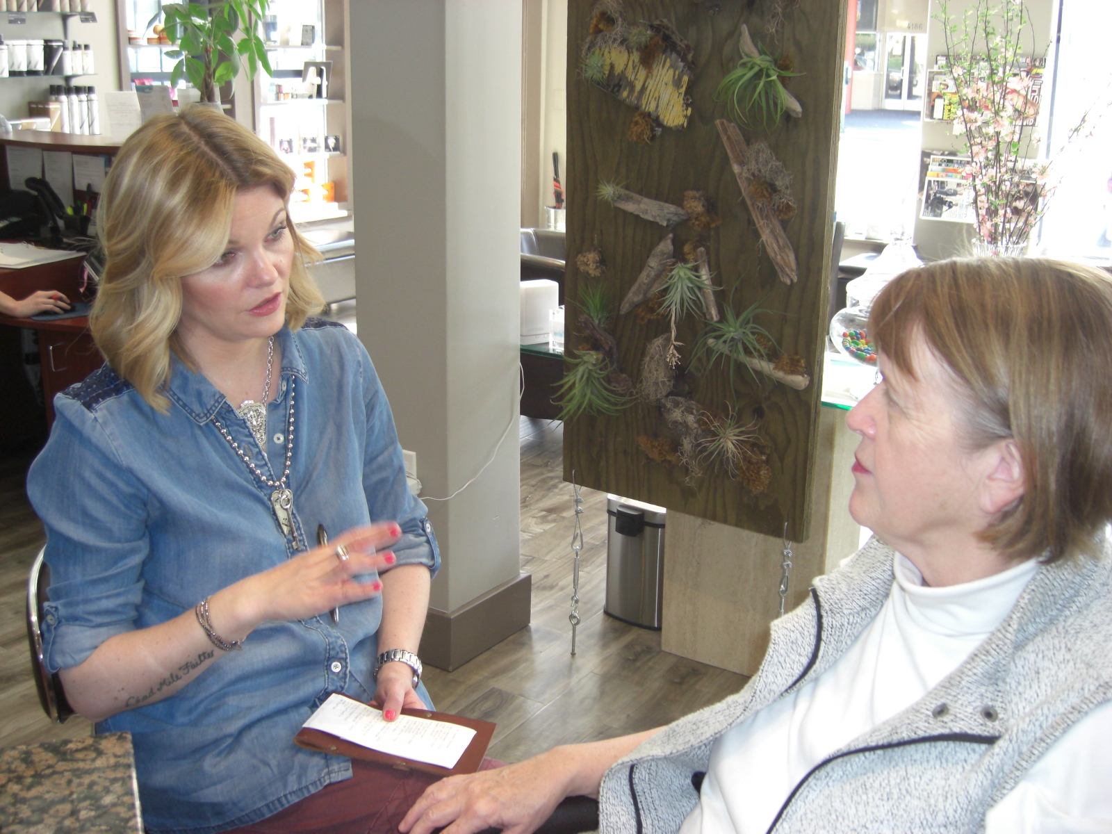 Eryn Harrison, owner of Calm A Salon in Oakland, California, consults with new client Marsha Hiscocks.