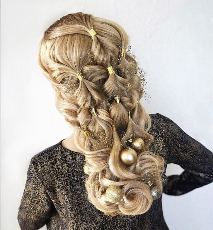 <p>Powell began by putting a halo hairband in the hair from Hairtalk and used serum from Scruples throughout the hair before curling with a large barrel curling iron. She then made mini ponytails scattered throughout the hair and created bubble braids securing them with gold braid jewelry. She added a foam hair insert at the bottom of the head to create volume in the curls then pinned them in place and added small glitter holiday ornaments as accents.</p>