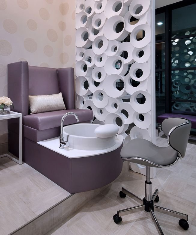 A pedicure throne with a view of the Maya Romanoff circle wall covering and the reversed bubble wood partition.