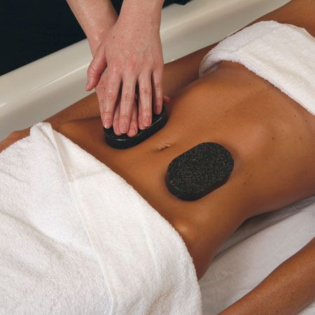 12. Based on client's preference, have her flip over for stone therapy with the warmed large oval stones on the abdomen. Gently press stones for deep relaxation.
