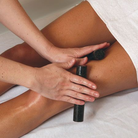 13. Using the warmed roller stones, glide lightly or deeply along legs. These stones may also be used on pressure points to ease stress and tension.