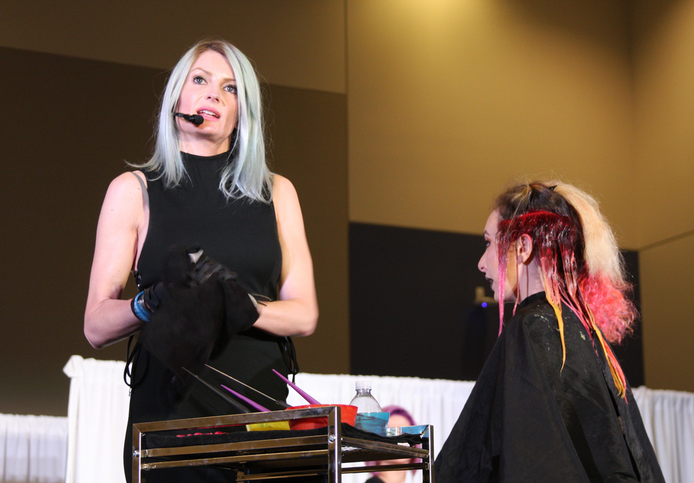 Alexis Thurston presents while applying color to her model on stage.