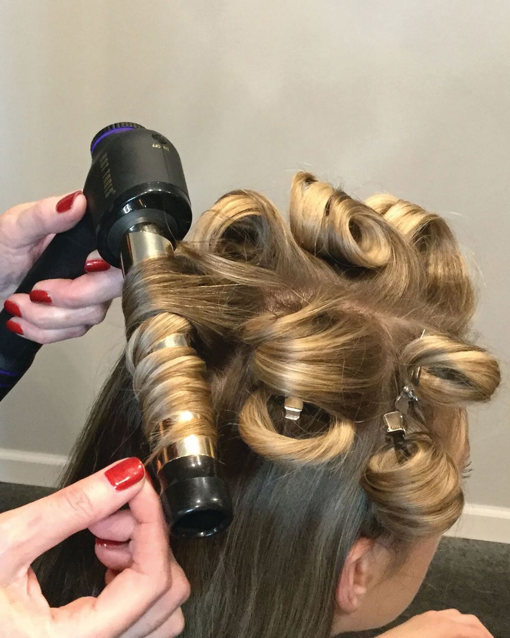 1. Wrap hair around the Curl Bar beginning near the handle. Twist the hair as you wrap to create spiral curls; the thickness of each curl will depend on the density of the hair.