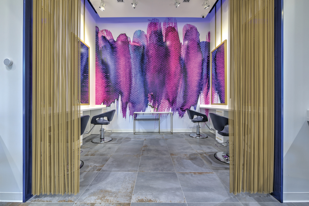 "Oh my, do we love a good color punch! <a href=""https://www.currentbynese.com/"" target=""_blank"" rel=""noopener"">Current Salon and Color Bar by Nese</a> in Ashburn, Virginia, exemplifies color with its two wall murals. The bright purple hues on the 14.9-foot ceilings create sophistication and a wow-factor like none other."