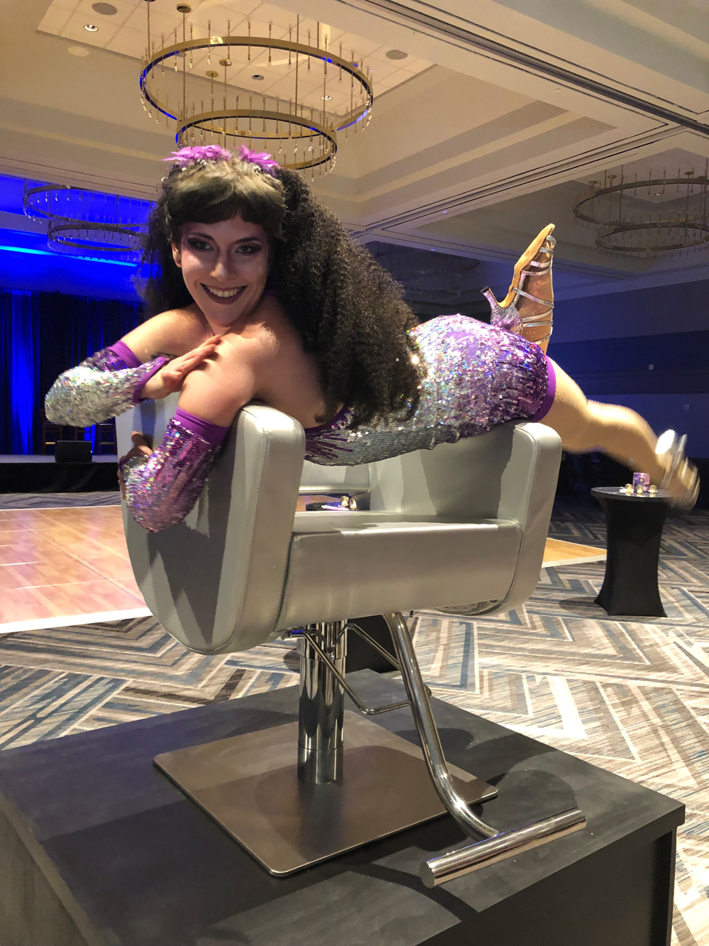 A acrobat poses on a Minerva chair at the DDSS recognition party hosted by Minerva.