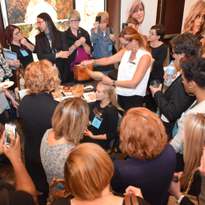 Attendees at the 2016 HAIR+ Summit crowd around the Easihair Pro booth, where Bobbi Russell...