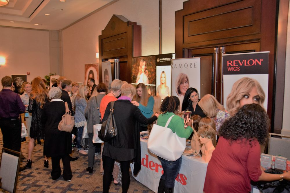 Attendees network with HAIR+ Summit sponsors during a break between presentations.