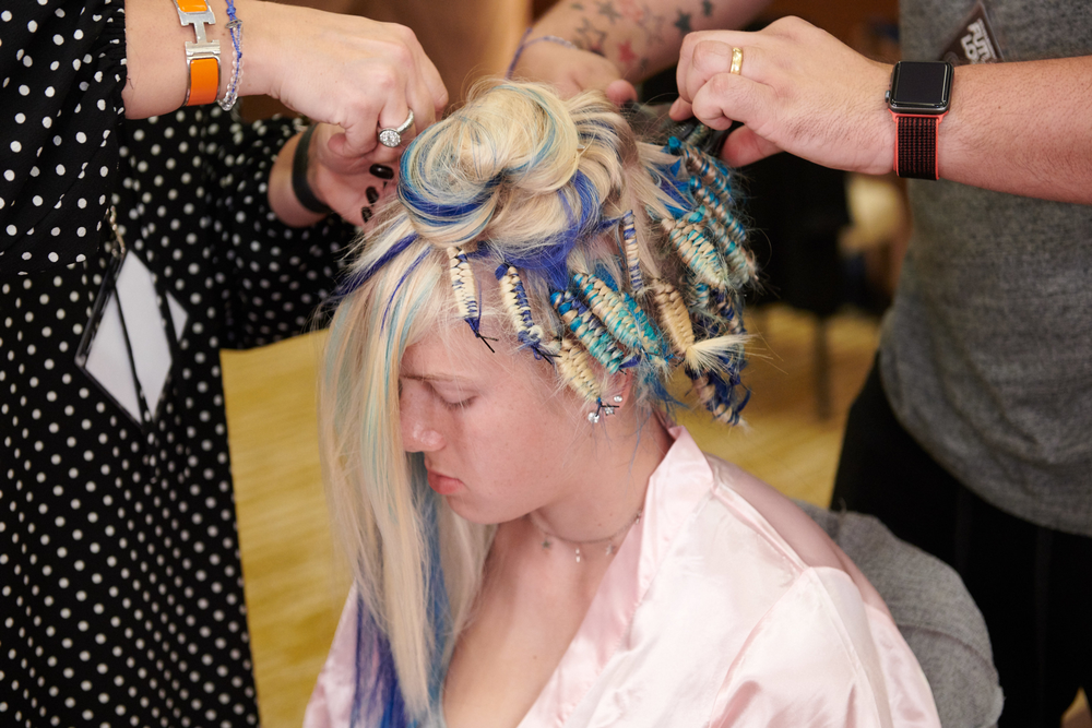 A model's hair is prepped in what will turn into a cloud-like shape on stage.