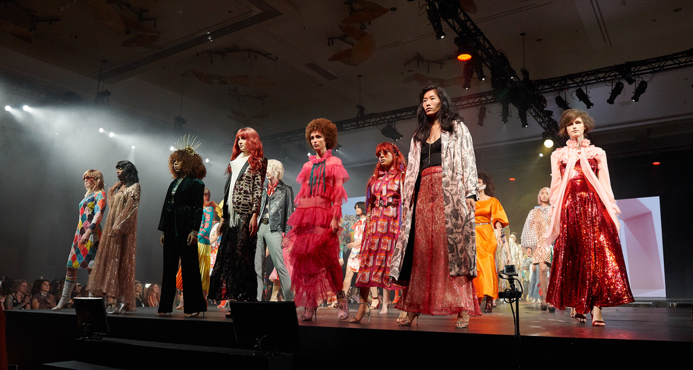 A parade of models takes the stage in colorful outfits and playful styles.