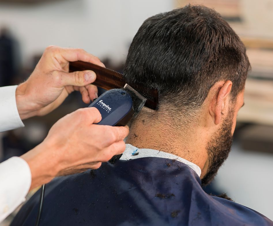 STEP 1 & 2: Start in the middle lower nape using The Classic Dual Comb. Hold the comb horizontally with The Classic Professional Clipper to create a taper fade.