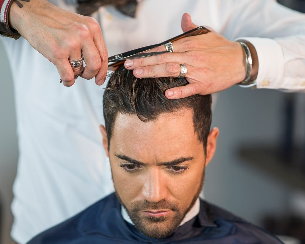 STEP 4: Take a middle parting at the highest point of the head and cut a guideline to the front by positioning your fingers horizontally.