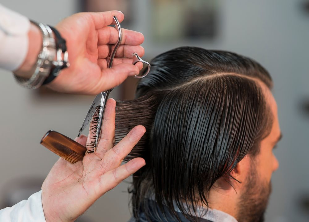 STEP 1: Create a horseshoe parting at the top of the head following the partial ridge. Next, create a guideline in the center back holding the hair at a 90 degree angle.
