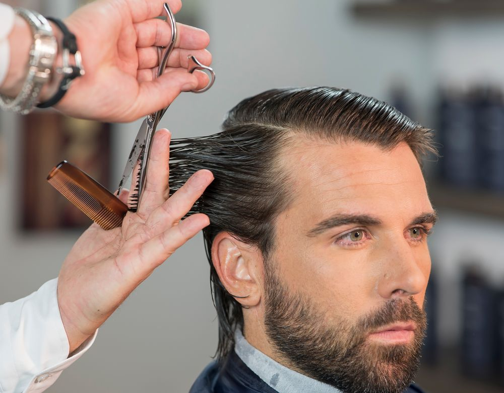 STEP 2: Cut the hair following a traveling guide from the center back to behind the ear.
