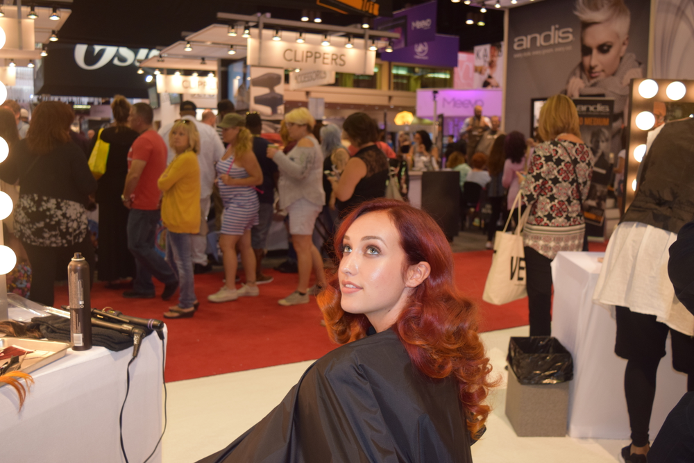 A model at the Kadus Professional booth. The day before, her hair was blonde. It was colored this red ombre hue using Kadus Professional haircolor.