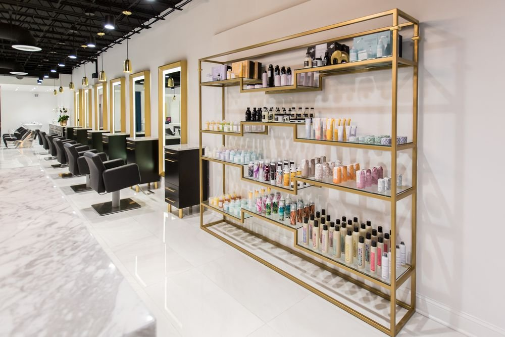 The custom-made glass retail shelving is framed in gold, and it creates a geometric design that captures the eye.