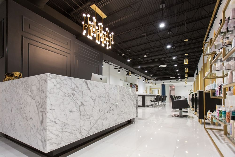 A white marble front desk contrasts nicely against the black wall with detailed carving.