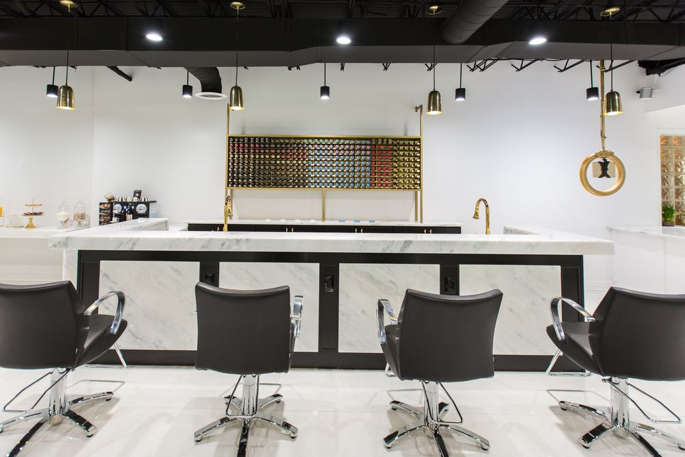 At the heart of the salon is the color bar with white marble countertop.