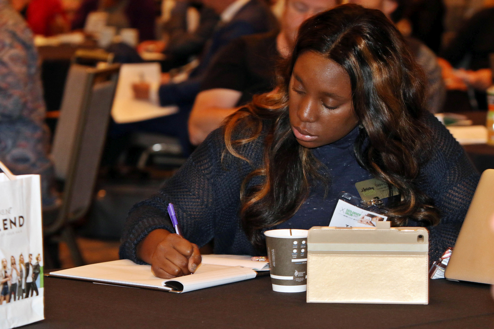 An attendee writes down her goals after a session.